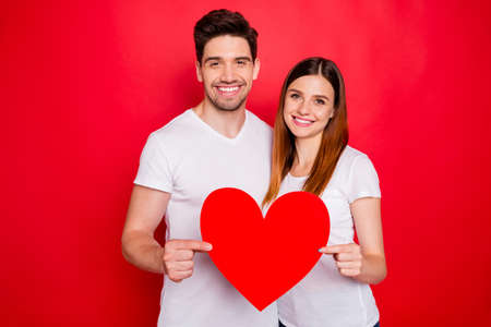 Photo of cheerful positive pretty cute nice couple of spouses holding big red white t-shirt heart smiling toothily showing their love isolated vivid color background
