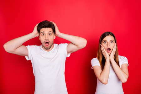 Photo of astonished amazed fearful boyfriend girlfriend people in white t-shirt having observed gossips of them spreading expressing stressful emotions on face isolated vibrant color background