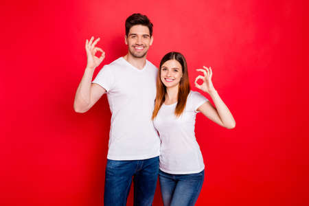 Photo of cheerful positive nice cute charming couple boyfriend girlfriend showing ok sign in jeans denim white t-shirt smiling toothily hugging isolated vivid color background 스톡 콘텐츠