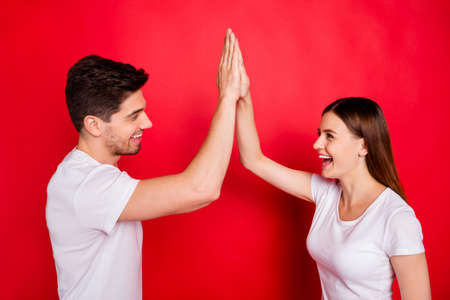 Photo of cheerful cute nice positive pretty boyfriend students girlfriend clapping their palms giving high five smiling toothily laughing in white t-shirts isolated vivid red color background