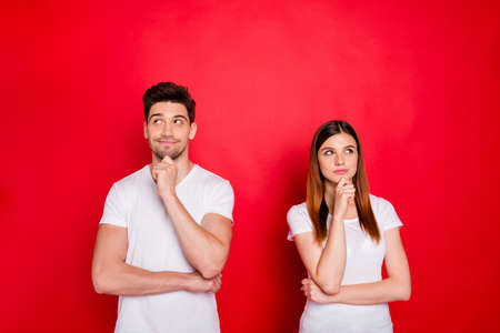Photo of redhair girlfriend and boyfriend wondered puzzled touching their chins wearing t-shirt white isolated red vivid color background 스톡 콘텐츠