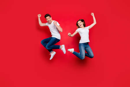 Full length body size photo of cheerful positive crazy excited overjoyed ecstatic couple boyfriend girlfriend screaming wearing jeans denim jumping white t-shirt isolated vivid color background 스톡 콘텐츠