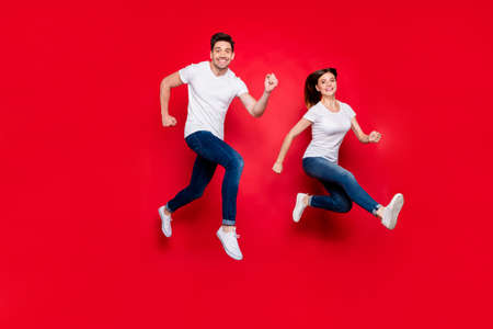 Turned full length body size photo of cheerful cute nice pretty girlfriend boyfriend spouses wearing jeans denim white t-shirt footwear smiling toothily running jumping isolated vivid color background