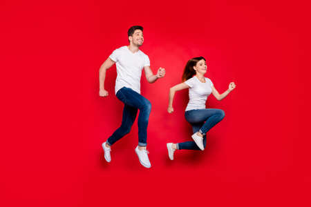 Turned photo of cheerful positive nice pretty cute couple boyfriend girlfriend wearing jeans denim white t-shirt smiling toothy footwear urgent for sales isolated over vivid color background