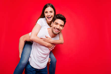 Photo of cheerful positive pretty couple of two people piggyback girl hugging riding guy in jeans denim white t-shirt carrying near empty space isolated vivid color background
