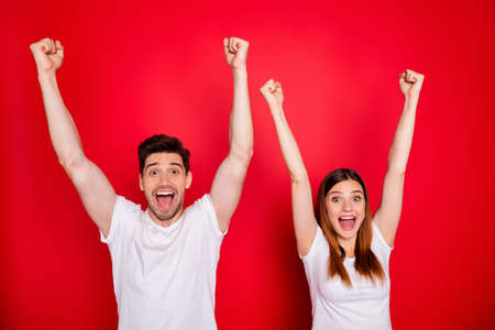Photo of cheerful excited students couple of two people expressing emotions on face in white t-shirt screaming yeah raising hand up boyfriend girlfriend happy together isolated bright color background 스톡 콘텐츠