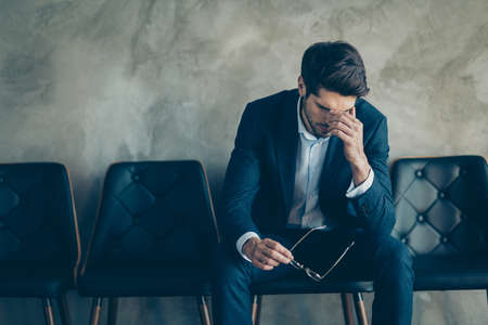 It is fail. Portrait of sad upset frustrated businessman sit on chair touch nose fingers have headache about his work mistake wait for boss argue wear blue blazer pants isolated grey color background Stock fotó