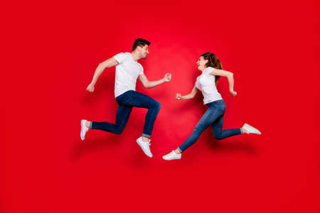 Side profile full length body size photo of cheerful positive pretty couple boyfriend girlfriend running into each other jumping jeans denim white t-shirt footwear isolated vivid color background 스톡 콘텐츠