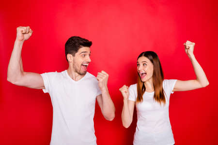 Photo of ecstatic overjoyed rejoicing students couple of people boyfriend girlfriend spouses demonstrating emotions on face expression screaming wearing white t-shirt isolated vivid color background 스톡 콘텐츠
