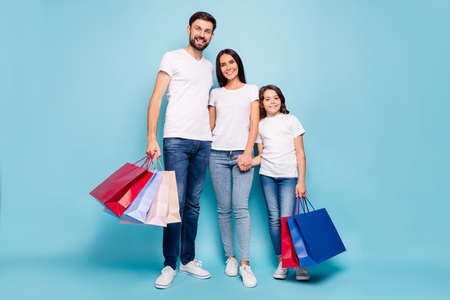 Full length photo of positive three people mommy daddy schoolkid addicted with brown hair shop hold hand hug embrace wear white t-shirt denim jeans sneakers isolated over blue color background
