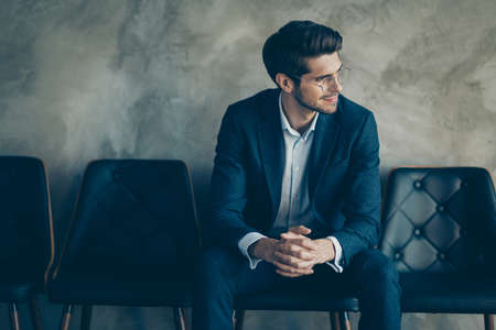 Profile side photo of dreamy freelancer sit on chair wait for appointment with human resources worker look window dream about new career wear stylish trousers blazer isolated grey color background Фото со стока