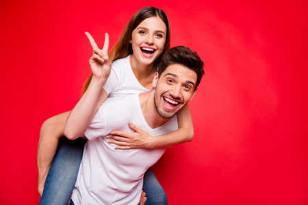 Photo of redhair positive nice pretty charming couple with girlfriend piggyback riding her boyfriend showing v-sign and him carrying her in jeans denim white t-shirt isolated vivid color background