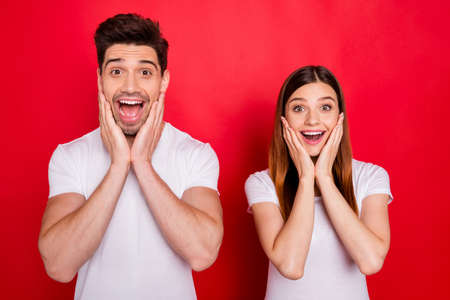 Photo of astonished friends funky funny girlfriend white t-shirt boyfriend having won lottery jackpot expressing excitement on faces screaming isolated vivid color background