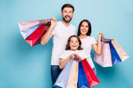 Portrait of excited positive cheerful three people mommy daddy schoolkid with brown hair shop center hold bags wear white t-shirt denim jeans isolated over blue color background