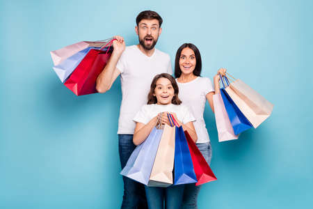 50 off. Real bargain concept. Portrait of excited three people mom dad schoolkid shop center hold bags scream wow omg wear white t-shirt denim jeans isolated over blue color background