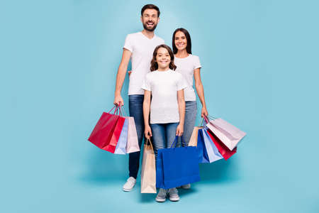 Full length photo of three people mom mommy dad daddy schoolkid shop retail on black friday wear white t-shirt denim jeans sneakers isolated over blue color background