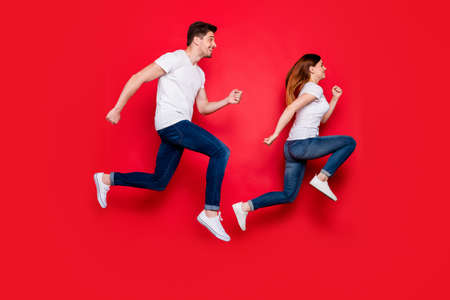 Full length body size side profile photo of cheerful positive running girlfriend boyfriend wearing jeans denim footwear white t-shirt smiling toothily isolated vivid color background jumping
