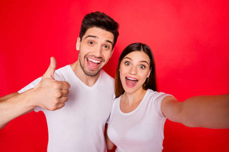 Photo of cheerful redhair nice pretty charming couple of girlfriend boyfriend smiling toothily showing in white t-shirt thumb up with excitement on face isolated vivid color background