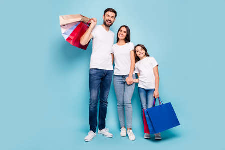 Full size photo of three clients people mom dad schoolkid with brown hair shop hug embrace hold hand bags black friday bargain wear white t-shirt denim jeans sneakers isolated blue color background 스톡 콘텐츠