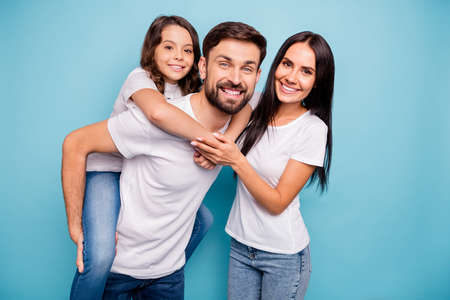 Portrait of positive cheerful funky three people carry kid piggyback enjoy weekends wear white t-shirt denim jeans denim isolated over blue color background