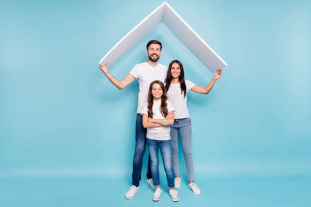 Mortgage house for full family. Full length photo of beautiful three people with brown hair school kid move new home wear white t-shirt denim jeans sneakers isolated over blue color background