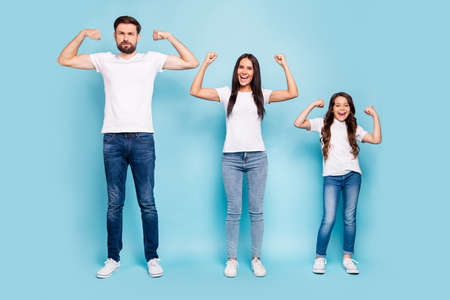 Full length photo of funky brave mommy daddy kid with brunette hair show triceps biceps enjoy enthusiastic wear white t-shirt denim jeans sneakers isolated over blue color background 스톡 콘텐츠