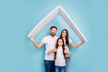 Portrait of beautiful three people mom dad school kid with brown hair hold roof move comfort cozy house approve feedback recommend wear white t-shirt denim jeans isolated over blue color background Zdjęcie Seryjne
