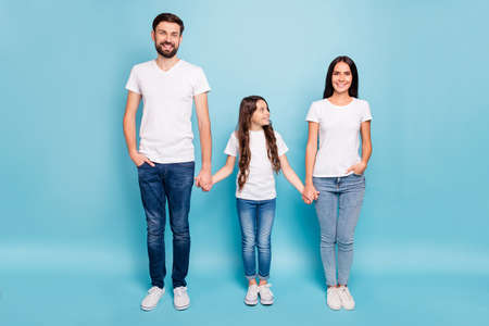 Full length photo of cheerful glad three people with brunette hair hold hand enjoy fun weekends relax rest wear white t-shirt denim jeans sneakers isolated over blue color background