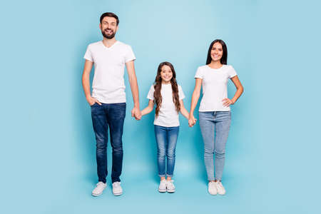 Full body photo of cheerful content big three people with brunette hair hold hand enjoy family day holidays wear white t-shirt denim jeans sneakers isolated over pastel blue color background