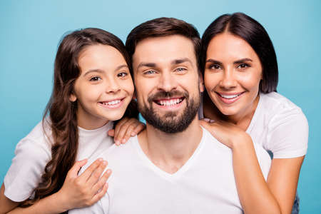 Close up photo of cheerful lovely three people piggyback lean shoulder enjoy vacation wear white stylish t-shirt isolated over blue pastel color background
