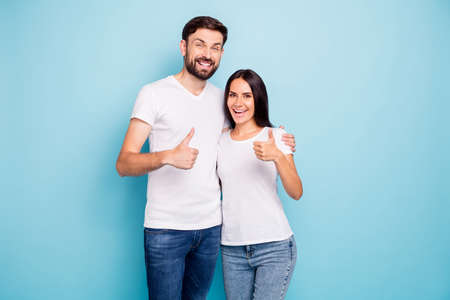Portrait of excited enthusiastic couple promoters show thumb up recommend choice adverts hug wear white t-shirt denim jeans good look isolated over blue color background Stock fotó