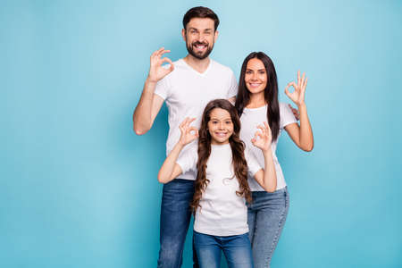 Portrait of positive content three promoters mom dad offspring with brunet hair show ok sign recommend sales ads wear white t-shirt denim jeans isolated over blue color background Imagens