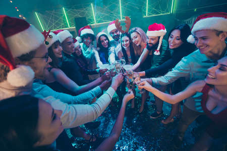 Photo of party crowd best friends holding sparkling wine glasses counting last seconds to newyear festive mood wear dresses shirts pants santa hat in night club
