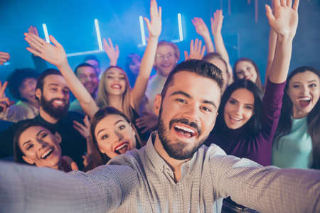 Close-up photo portrait of large crowd cheerful wit toothy beaming smile bearded youth youngster in fog smoke neon lights celebrating birthday taking selfie Stock Photo