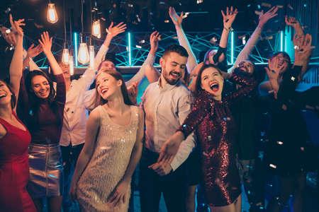 Foto di persone che ballano vestite con abiti da cerimonia che si rallegrano del buon tempo libero insieme a un macho circondato da ragazze che bazzicano tra di loro in coriandoli che cadono Archivio Fotografico