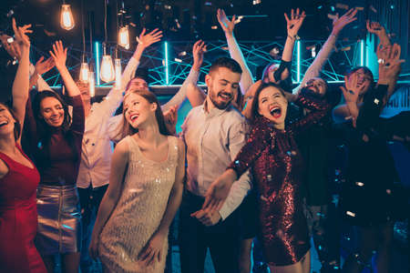 Foto von tanzenden Menschen in festlicher Kleidung, die sich zusammen mit Macho über eine gute Freizeit freuen, umgeben von Mädchen, die zwischen ihnen in fallendem Konfetti hängen Standard-Bild
