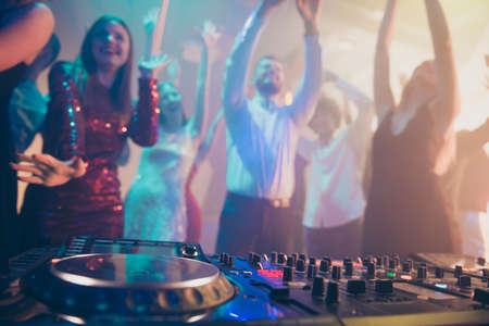 Dj performing loud stereo sound rhythm trance techno electronic style set music for attractive stylish cheerful positive crowd having fun visiting concert at fashionable modern nightclub