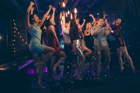 Foto van de volledige lengte van het lichaam van vrolijke charmante mooie jonge mensen die plezier hebben in de nachtclub die dansen in vallende confetti-regen die onder lichten staat