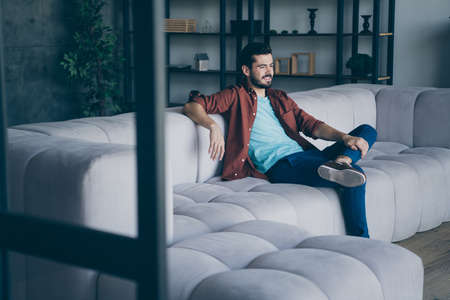 Photo of handsome guy watching happening in living room sitting comfortable couch relax saturday evening in modern flat loft indoors casual dressed