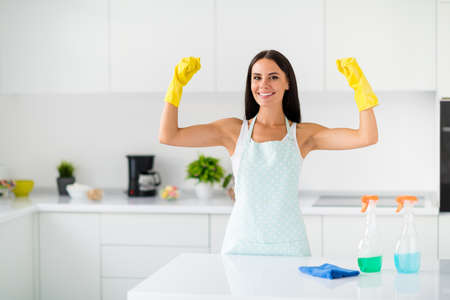 Superhero for dirty rooms. Brunetthair girl wearing yellow rubber gloves show muscles advertise she can clean wash polish all furniture in kitchen indoors