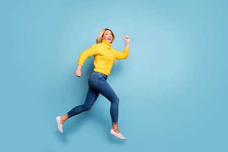 Pełnej długości zdjęcie profilowe szalonej pani skaczącej wysokiej pośpiechu centrum handlowego czarny piątek sprzedaż nosić dzianiny żółty sweter dżinsy na białym tle niebieski kolor tła