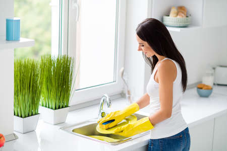 Profile side back rear side photo of positive cheerful girl wash plates use yellow rubber protection gloves sponge stay near window in house kitchen