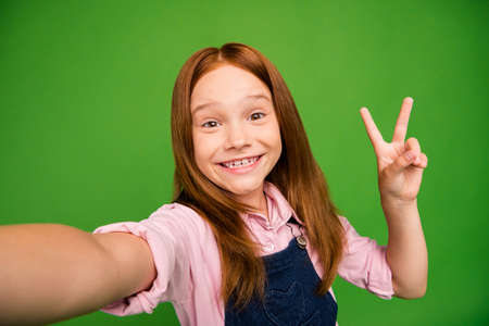 Close up photo of pretty little foxy schoolchild showing v-sign symbol making selfies excited cheerful mood wear denim overall pink shirt isolated green background