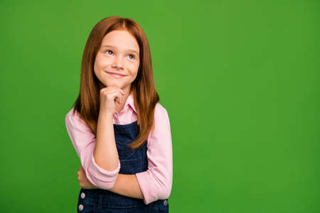 Photo of adorable little ginger school child in front of blackboard dream to meet classmates 1 september classroom wear denim overall pink shirt isolated green background