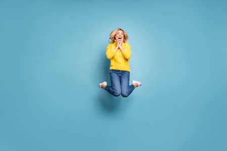 Full body photo of crazy lady jumping high celebrating free trip abroad rejoicing hands on cheekbones wear knitted yellow pullover jeans isolated blue color background