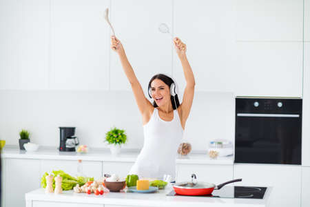 Portrait of funky cheerful housewife girl real chef listen music on her headset dance sing volume radio song while cooking health care supper raise kitchen utensils in white house