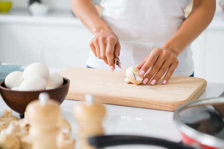 Cropped close up photo of stylish woman gourmet veggie cut mushroom on chopping board prepare fest have bowl with fresh eggs in house white kitchen
