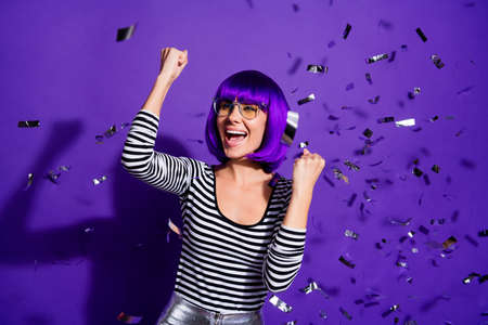 Portrait of excited pretty lady raising fists screaming yeah isolated over purple violet background Standard-Bild