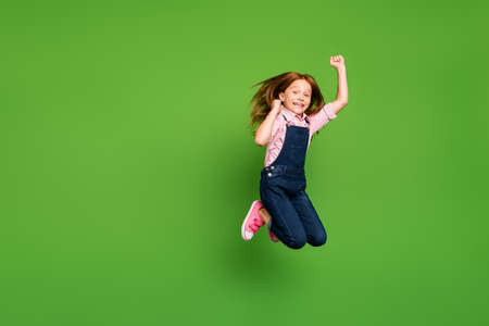Full length photo of funny pretty little schoolchild jumping high rejoicing summer holidays beginning wear casual denim overall pink shirt isolated green background Imagens