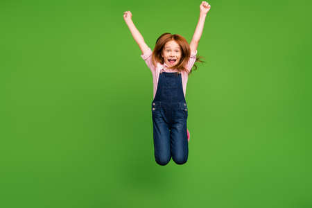 Full body photo of cheerful pretty little schoolchild jumping high rejoicing summer holidays weekend wear casual denim overall pink shirt isolated green background